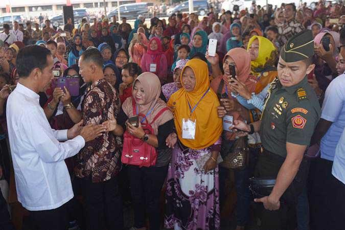 Presiden Joko Widodo (kiri) berjabat tangan dengan pelaku UMKM nasabah Mekaar binaan Permodalan Nasional Madani (PNM) setibanya di Lapangan Cepoko, Kecamatan Panekan, Kabupaten Magetan, Jawa Timur, Jumat (1/2/2019). - ANTARA/Akbar Nugroho Gumay