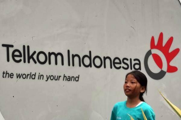 Pejalan kaki berjalan melewati logo Telkom di Jakarta, Senin (27/11). - JIBI/Dedi Gunawan