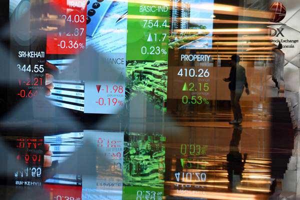 Seorang pria melintasi layar elektronik pergerakan harga saham di Bursa Efek Indonesia, Jakarta, Jumat (19/10/2018). - ANTARA/Akbar Nugroho Gumay