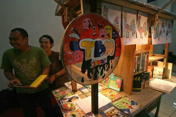 Warga membaca buku koleksi taman baca masyarakat Gelaran Jambu di Monumen Simpang Lima Gumul, Kediri, Jawa Timur, Jumat (24/3) malam. - Antara