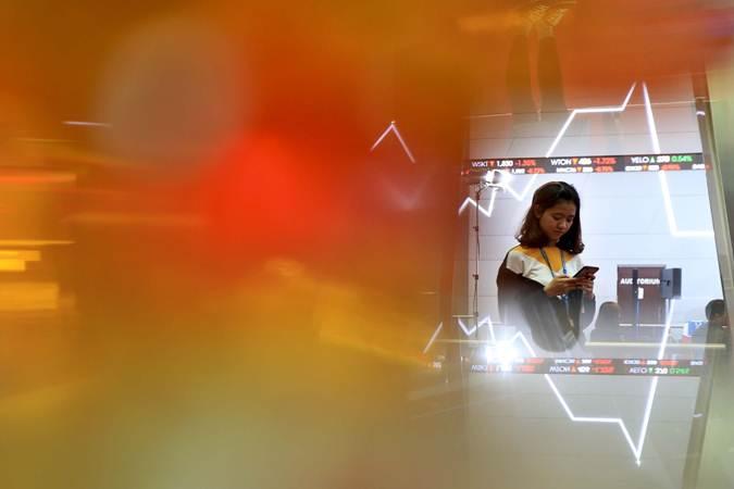 Karyawati berkomunikasi di dekat monitor pergerakan Indeks Harga Saham Gabungan (IHSG) di Bursa Efek Indonesia, Jakarta, Jumat (22/2/2019). - Bisnis/Nurul Hidayat