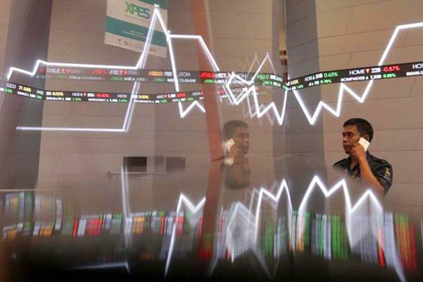 Karyawan berkomunikasi di dekat papan elektronik yang menampilkan pergerakan indeks harga saham gabungan (IHSG) di Bursa Efek Indonesia, Jakarta, Kamis (12/10). - JIBI/Nurul Hidayat