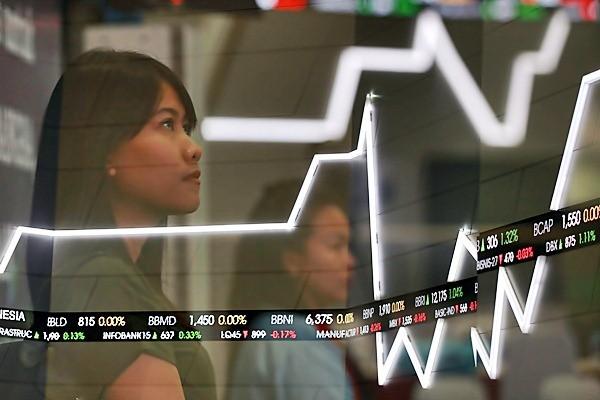 Karyawati beraktivitas di dekat papan elektronik yang menampilkan pergerakan Indeks Harga Saham Gabungan (IHSG) di Bursa Efek Indonesia. - JIBI/Abdullah Azzam