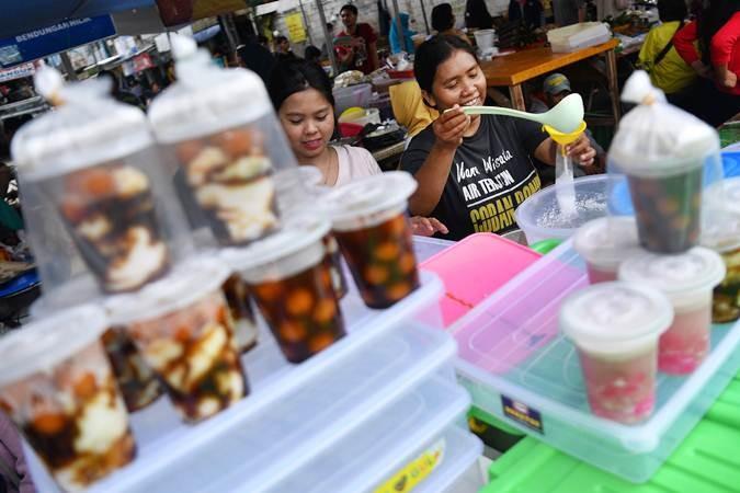 Pedagang membungkus minuman untuk dijual di Pasar Takjil Benhil, Jakarta, Senin (6/5/2019). - ANTARA/Sigid Kurniawan
