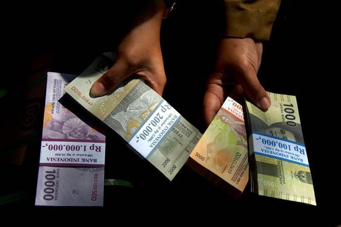 Warga menunjukkan uang rupiah pecahan kecil di Lapangan Karebosi, Makassar, Sulawesi Selatan, Senin (13/5/2019). - ANTARA/Abriawan Abhe