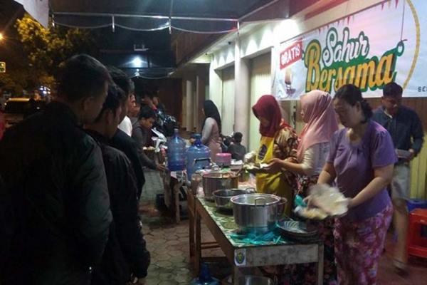 """Sejumlah warga mengantre hidangan makan sahur gratis yang disediakan pengusaha tekstil """"Laris Group"""" di Purwokerto, Kabupaten Banyumas, Jawa Tengah, Rabu (15/5/2019) dini hari. - Antara"""