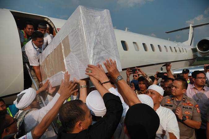 Jemaah membawa peti berisi jenazah ustaz Arifin Ilham yang baru tiba dari Penang, Malaysia di Bandara Halim Perdanakusuma, Jakarta Timur, Kamis (23/5/2019). - ANTARA/Deka Wira