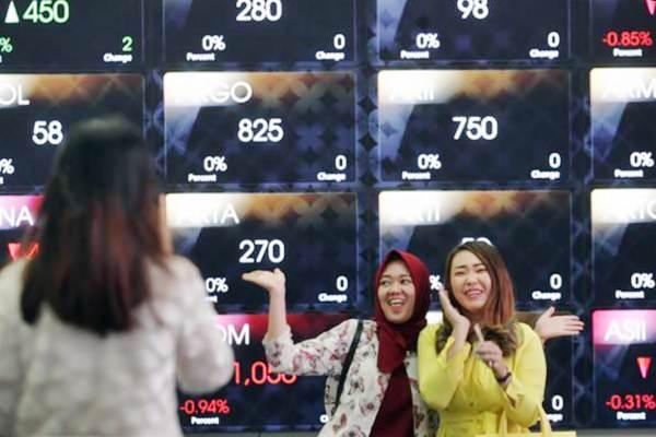 Pengunjung menggunakan ponselnya di dekat papan elektronik yang menampilkan perdagangan harga saham di gedung Bursa Efek Indonesia (BEI), Jakarta, Senin (28/8). - JIBI/Dedi Gunawan