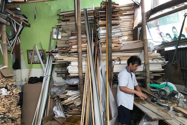 Pekerja tengah memotong bahan bingkai di rumah produksi Delapan Bingkai, Depok./Sandi Purnomo - Bisnis
