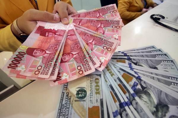 Karyawan bank memperlihatkan uang pecahan Dolar AS dan Rupiah di Jakarta - ANTARA/Rivan Awal Lingga