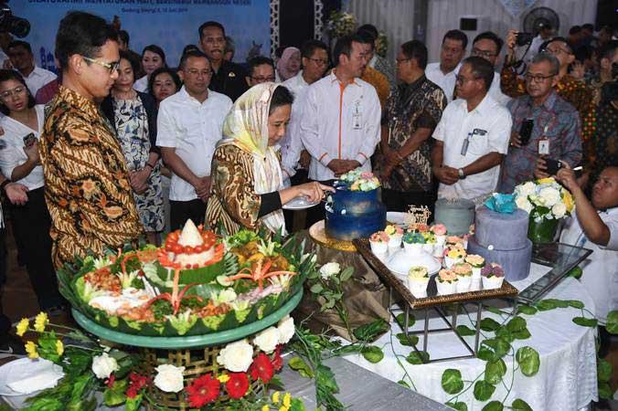 Menteri BUMN Rini Soemarno (tengah) memotong kue saat menerima kejutan ulang tahun di sela-sela acara halalbihalal di Kementerian BUMN, Jakarta, Senin (10/6/2019). - ANTARA/Akbar Nugroho Gumay