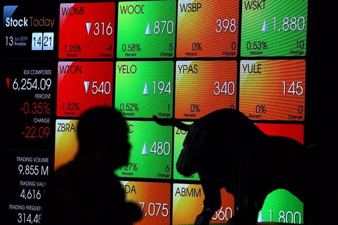 Siluet karyawan di dekat layar monitor pergerakan Indeks Harga Saham Gabungan (IHSG) di Bursa Efek Indonesia, Jakarta, Kamis (13/6/2019). - Bisnis/Nurul Hidayat