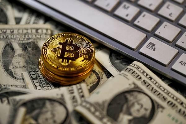 Ilustrasi Bitcoin diletakkan di atas lembaran uang dolar AS. - REUTERS/Dado Ruvic