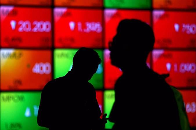 Siluet karyawan di dekat layar monitor pergerakan Indeks Harga Saham Gabungan (IHSG) di Bursa Efek Indonesia, Jakarta