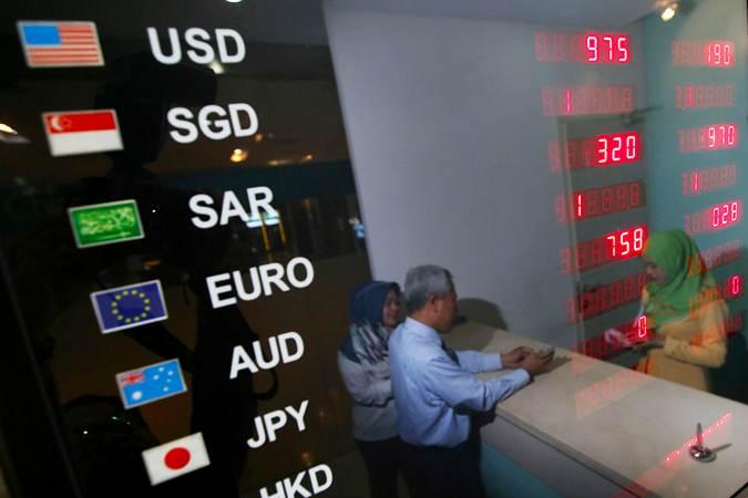 Karyawan melayani nasabah yang melakukan penukaran mata uang di Money Changer Mandiri Syariah Thamrin, Jakarta, Selasa (2/7/2019). - Bisnis/Abdullah Azzam