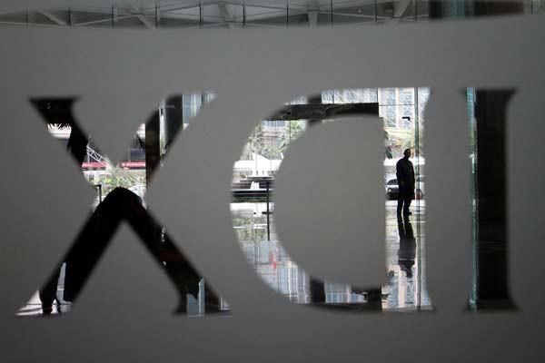 Siluet karyawan melintasi logo IDX Indonesia Stock Exchange di gedung Bursa Efek Indonesia Jakarta, Senin (6/7). - Bisnis.com / Dwi Prasetyo