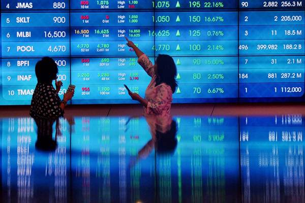 Karyawati berkomunikasi di dekat monitor pergerakan Indeks Harga Saham Gabungan (IHSG) di Bursa Efek Indonesia, Jakarta, Selasa (3/7/2018). - Bisnis/Nurul Hidayat