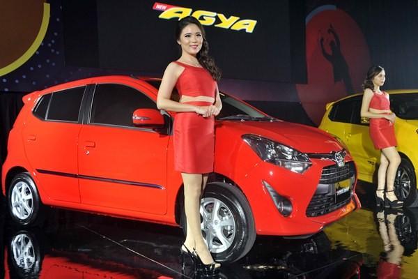 Model berfoto dengan kendaraan Toyota New Agya. - Antara/Audy Alwi