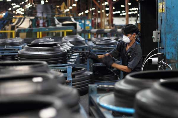 Seorang karyawan tengah menyelesaikan proses produksi ban Goodyear. - goodyear