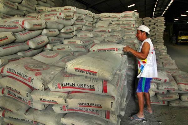Pekerja membongkar tumpukan karung Semen Gresik, di sebuah gudang distributor PT Semen Indonesia (Persero) Tbk, di Banjarmasin, Kalimantan Selatan, Rabu (12/12/2018). - Bisnis/Wahyu Darmawan