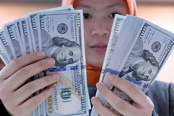 Karyawan sebuah bank memegang mata uang dollar Amerika Serikat di Jakarta, Rabu (11/1/2017). - JIBI/Abdullah Azzam