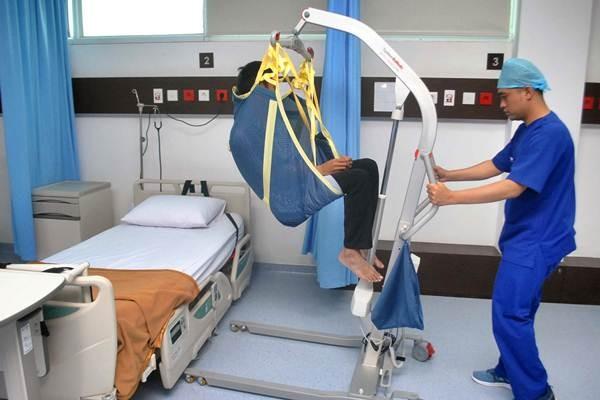 Petugas medis menunjukkan cara kerja alat untuk mengangkat dan memindahkan pasien penyakit stroke saat peresmian pelayanan dan kunjungan media di Rumah Sakit Siloam, jalan Pajajaran, Kota Bogor, Jawa Barat, Selasa, (18/7). - ANTARA/Arif Firmansyah
