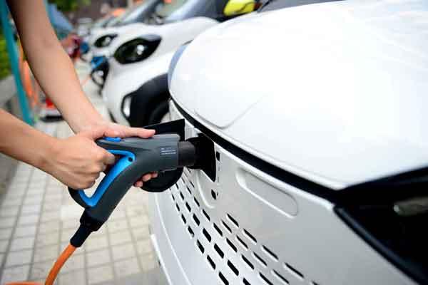 Seorang petugas memasukkan kabel pengisian ke mobil listrik - Reuters
