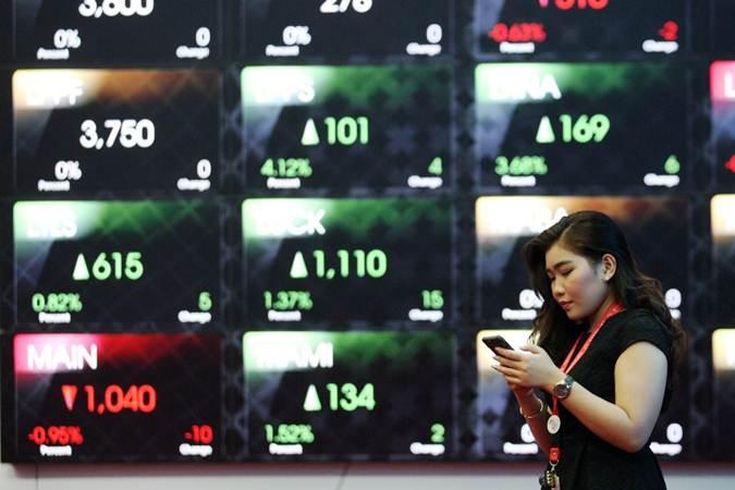 Pengunjung menggunakan ponsel di dekat papan elektronik yang menampilkan perdagangan harga saham di BEI, Jakarta, Selasa (11/6/2019). - Bisnis/Dedi Gunawan