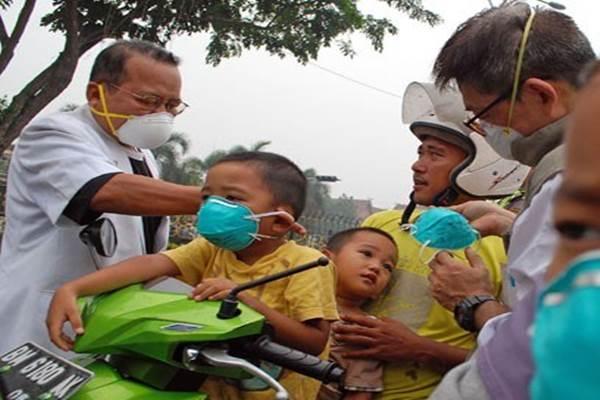 Dokter Ikatan Dokter Indonesia (IDI) Cabang Pekanbaru membagikan masker pelindung pernapasan kepada pengguna jalan raya di Pekanbaru, Riau - Antara