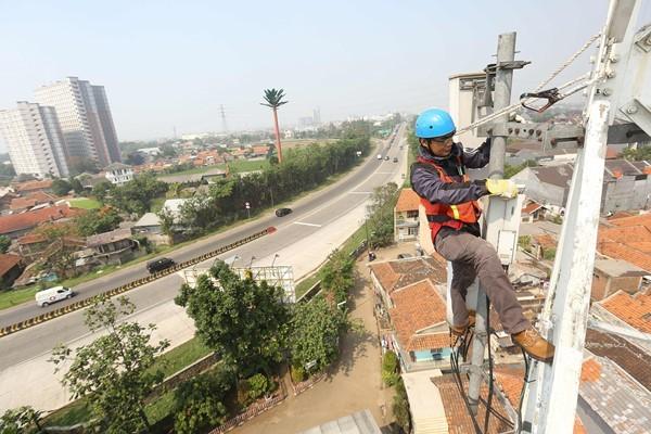 Teknisi melakukan perawatan base transceiver station (BTS) di area Jawa Tengah