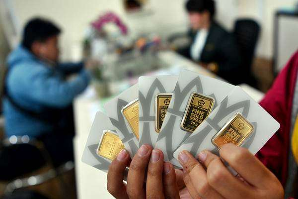 Konsumen menunjukkan emas batangan yang dibelinya di Butik Emas Logam Mulia, Gedung Aneka Tambang, Jakarta, Selasa (8/1/2019). - ANTARA/Sigid Kurniawan