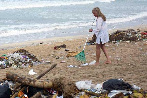 Wisatawan mancanegara (wisman) membersihkan sampah yang berserakan di kawasan Pantai Kuta, Badung, Bali, Selasa (1/1/2019). - ANTARA/Nyoman Hendra Wibowo