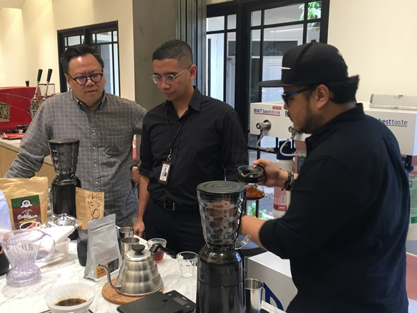 General Manager ABCD School of Coffe, Willyanto (kanan) dan Muhammad Gumilang (tengah) selaku Senior Vice President Retail Deposits Product and Solution Bank Mandiri sedang meroasting kopi. - Bisnis/Akbar Evandio