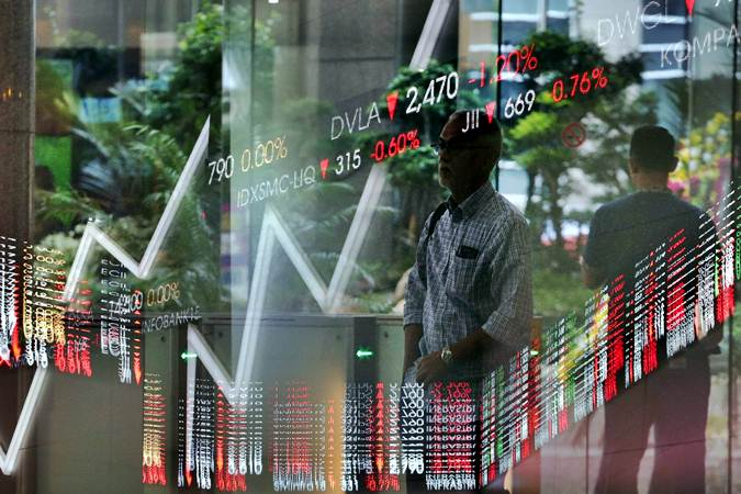 Karyawan melintas di dekat layar penunjuk pergerakan Indeks Harga Saham Gabungan (IHSG) di gedung Bursa Efek Indonesia di Jakarta - Bisnis/Felix Jody Kinarwan
