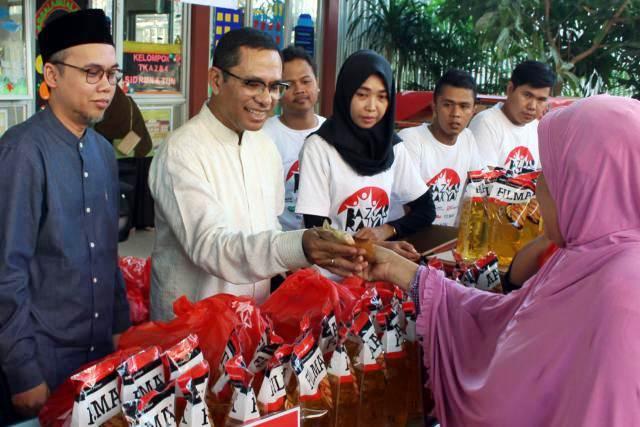 Ketua Umum Yayasan Muslim Sinar Mas Saleh Husin (kedua kiri) didampingi Ketua III Direktorat Bisnis dan Ekonomi Pesantren Tahfizh Daarul Quran Tarmizi Ash Shidiq (kiri) melayani warga saat bazar rakyat di Tangerang, Jumat (24/5/2019). - Bisnis/Abdullah Azzam