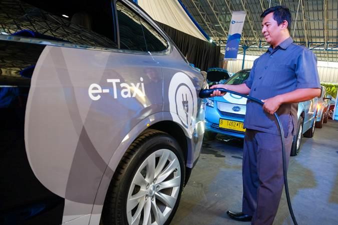 Pengemudi mengisi daya taksi bertenaga listrik Bluebird di sela-sela peluncurannya di Jakarta, Senin (22/4/2019). - Bisnis