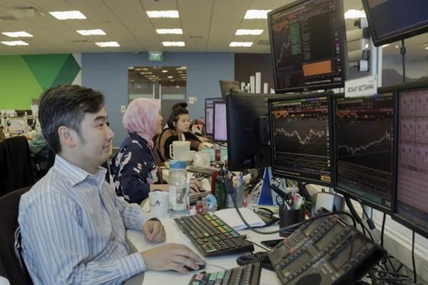 Karyawan mengamati pergerakan Indeks Harga Saham Gabungan (IHSG) di Dealing Room Bank Permata, Jakarta, Rabu (4/4/2018). - Bisnis/Felix Jody Kinarwan