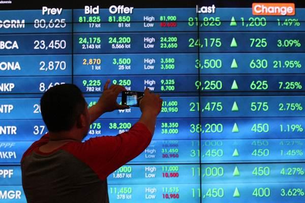 Pengunjung mengabadikan papan elektronik yang menampilkan perdagangan harga saham, di Jakarta, Senin (19/2/2018). - Bisnis/Dedi Gunawan