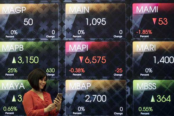 Karyawati melintas di depan layar pergerakan Indeks Harga Saham Gabungan (IHSG) di gedung Bursa Efek Indonesia, Jakarta, Kamis (22/6). - Antara/M Agung Rajasa