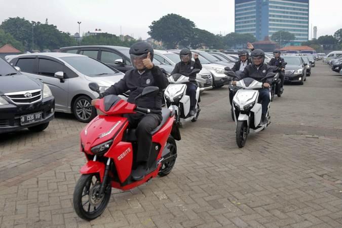 Menristekdikti Mohamad Nasir (kiri) mengendarai sepeda motor listrik menuju lokasi acara Indonesia Startup Summit 2019 di JIExpo Kemayoran, Jakarta, Rabu (10/4/2019). - Bisnis/Felix Jody Kinarwan