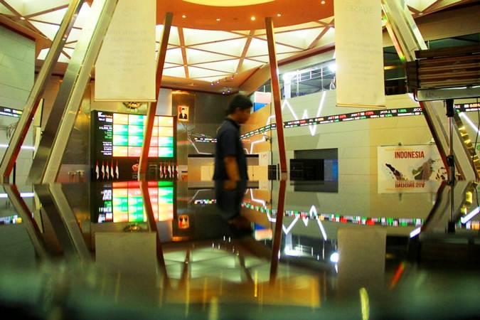 Pengunjung berjalan di dekat papan pergerakan Indeks Harga Saham Gabungan (IHSG) di kantor Bursa Efek Indonesia, Jakarta, Senin (10/6/2019). - Bisnis/Triawanda Tirta Aditya