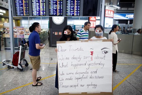 Pengunjuk rasa anti pemerintah meminta maaf atas kerusuhan yang terjadi di bandara Hong Kong, China, Rabu (14/8/2019). - Reuters/Thomas Peter