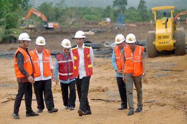 Presiden Joko Widodo (ketiga kanan), didampingi Menteri PUPR Basuki Hadimuljono (kedua kiri), Dirut Hutama Karya, I Gusti Ngurah Putra (kiri), Gubernur Sumbar Irwan Prayitno (kanan), Gubernur Riau Arsyadjuliandi Rachman (kedua kanan), dan Bupati Padangpariaman, Ali Mukhni meninjau lokasi groundbreaking jalan tol Sumbar - Riau, di Kab.Padangpariaman, Sumatra Barat, Jumat (9/2/2018). - ANTARA/Iggoy el Fitra
