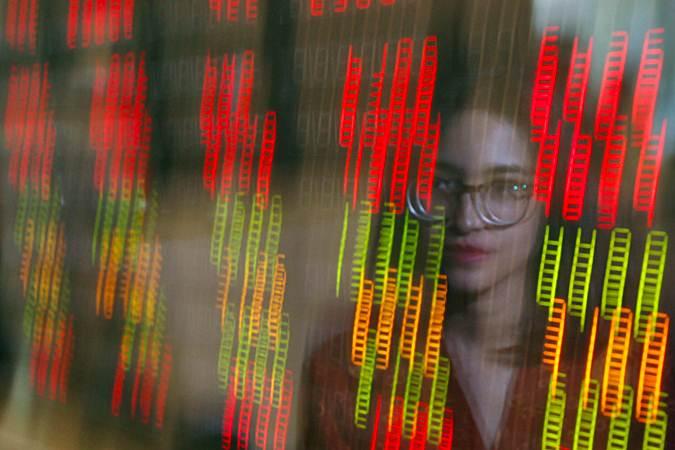 Karyawan berada di depan papan elektronik yang menampilkan harga saham di Jakarta, Senin (22/7/2019). - Bisnis/Abdullah Azzam