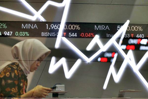Karyawan beraktivitas di dekat papan elektronik yang menampilkan pergerakan IHSG di Bursa Efek Indonesia, Jakarta, Senin (27/11). - JIBI/Abdullah Azzam