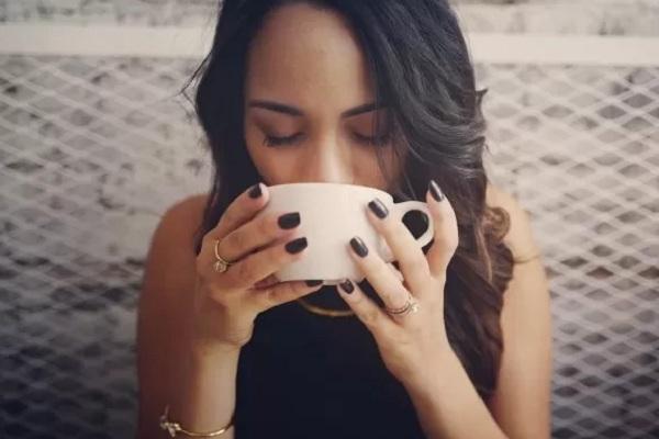 Seorang wanita sedang menikmati secangkir kopi. - Antara