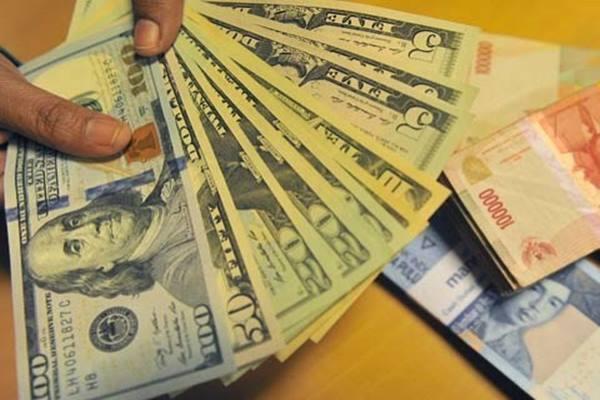 Karyawan menghitung pecahan uang dolar Amerika di Jakarta. - Antara