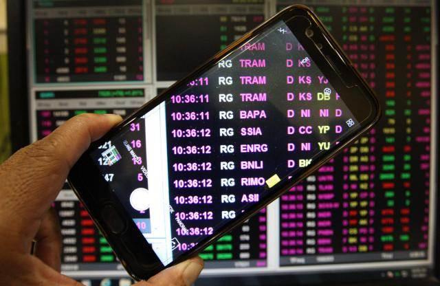 Pengunjung mengambil foto monitor perdagangan harga saham di Jakarta - Bisnis/Dedi Gunawan
