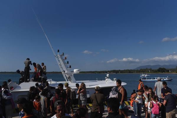 Sejumlah wisatawan mancanegara menuruni kapal cepat ketika tiba di Pelabuhan Bangsal, Lombok Utara, NTB, Senin (6/8). Sedikitnya 700 orang wisatawan bersama warga setempat dievakuasi dari Gili Trawangan, Gili Air dan Gili Meno menuju Pelabuhan Bangsal mengantisipasi terjadinya gempa susulan. - Antara