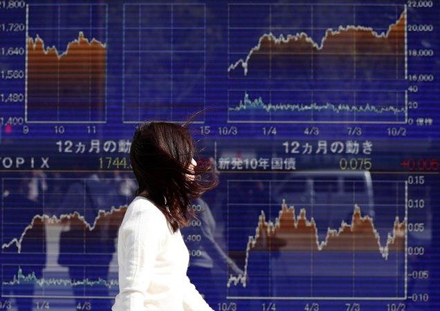 Seorang wanita berjalan melewati papan elektronik yang menunjukkan grafik pergerakan indeks Nikkei Jepang baru-baru ini. - Reuters
